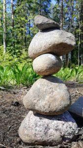 Viisi vaaleaa luonnon kiveä, jotka kasattu torniksi. Kuvituskuva.